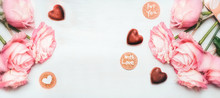 Romantic Pink Roses Bunch With Chocolate In Shape Of Heart And Cards With Lettering With Love For You On White Wooden Background, Top View, Banner