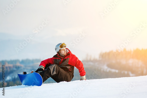 Poster Wintersporten Snowboarder wearing helmet, red jacket, gloves and pants sitting on snowy slope on top of a mountain looking away, with an astonishing view on hills. Carpathian mountains