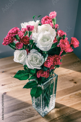Fotografija  Bouquet of white roses and cloves in glass vase