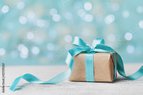 Fotografie, Obraz  Christmas gift box against turquoise bokeh background