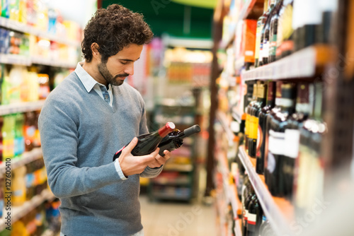Fotografie, Obraz Man choosing a wine bottle
