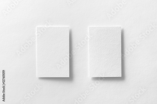 Mockup of two vertical business cards at white textured paper