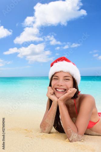 da4da891b8d2a Merry Christmas santa hat woman on beach vacation holiday season. Happy  Asian multiracial woman smiling wearing santa hat lying down on beach  relaxing .