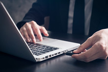 Close Up Of Businessman Using Flash Drive Connect To Laptop On The Desk.