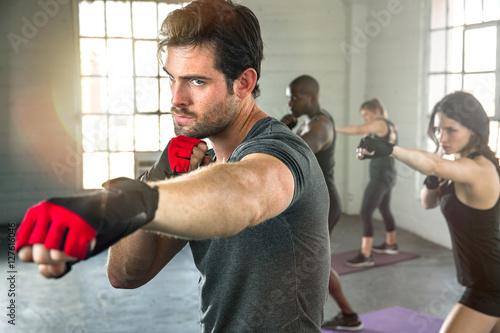 Láminas  Intense focused man serious expression punching boxing workout throwing fist wit