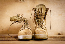 Old Brown Military Boots On A Wooden Table