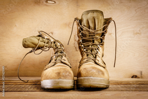 Fotografering  old brown military boots on a wooden table