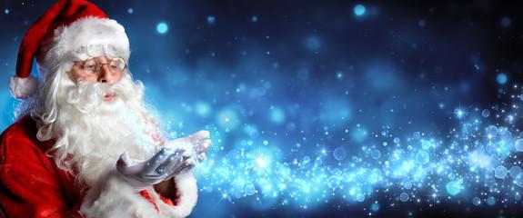 Santa Claus Blowing Magic Christmas Stars In Snowy Night