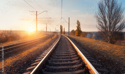 Poster Voies ferrées Railway station against beautiful sky at sunset. Industrial landscape with railroad, blue sky with clouds, sun, trees and grass. Railway junction in countryside of Ukraine. Heavy industry. Travel