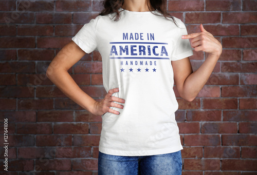 Woman in white t-shirt with text MADE IN AMERICA HANDMADE on brick wall background Poster Mural XXL