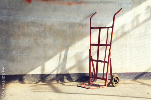 Red empty sack barrow or hand truck dolly  Beside old walls back Fototapete