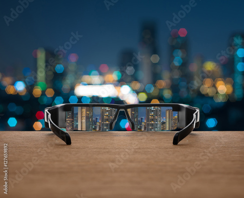 ee50678503 Cityscape focused in glasses lenses on the wooden over the abstr ...