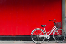 A Sivler Bike Parking In Front Of A Red Wall.