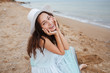 Cheerful lovely young woman sitting and smiling on the beach