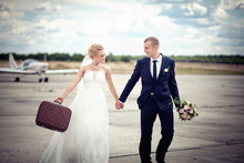 Young Couple Just Married With A Suitcase Running On Airplane