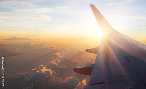 View of the sunset,clouds and airplane wing from the Inside