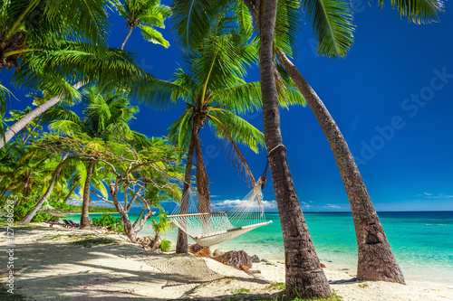 Deurstickers Tropical strand Empty hammock in the shade of palm trees on tropical Fiji Island