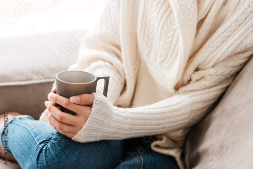 Woman with cup of coffee sitting on sofa at home Fototapet