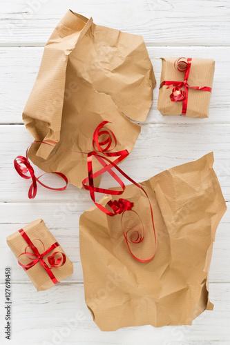 Fotografia, Obraz  Weihnachtsgeschenke auspacken auf einem weißen Holztisch