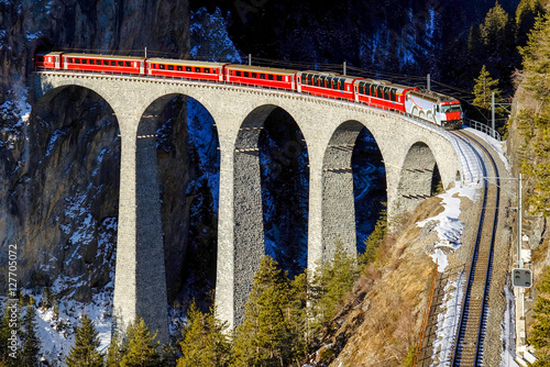 Fototapeta  Train goes over bridge among mountains