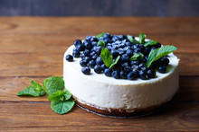 Sweet Creamy Blueberry Cheesecake With Fresh Blueberries And Mint Leaves On A Wooden Background With Copy Space.