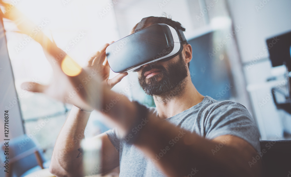 Fototapeta Closeup of bearded young man wearing virtual reality goggles in modern coworking studio. Smartphone using with VR headset. Horizontal, blurred.