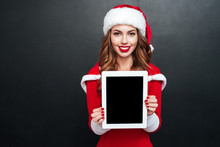 Cheerful Woman In Santa Claus Hat Showing Blank Screen Tablet