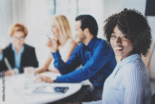 Portrait of pretty african american business woman with afro smiling at the camera.Coworking team in brainstorming process on background in meeting room. Horizontal,blurred.
