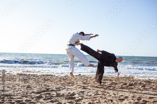 Fotomural karate sparing on the beach sea background