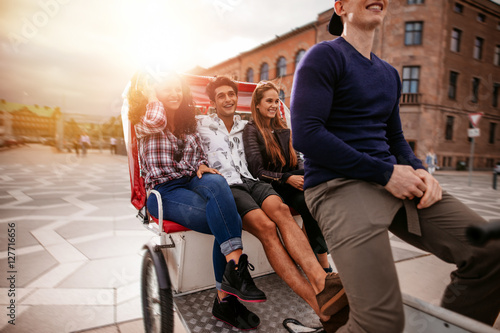 Fotografie, Obraz  Teenagers riding on tricycle and having fun
