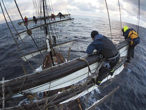 Valokuva  sailors aloft furling sails on a traditional tallship or squarerigger
