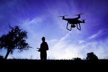 Silhouette Of Man With Flying Drone In Nature At Dusk.