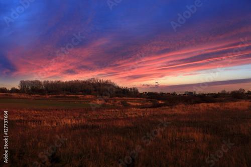 Fototapeta Kolorowy zachód słońca nad polami, wioską. obraz