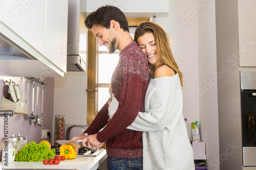 Fotografia, Obraz  Loving couple cooking together in the kitchen at home
