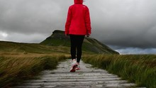 Tracking Shot Of A Woman In Outdoor Clothes Walking On The Boardwalk. Pen-Y-Ghent In Yorkshire Dales On Background.