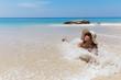 slim brunette woman in hat on beach