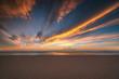 Sandy beach, colorful sunrise with beautiful cloudscape