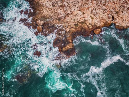 Valokuva  Aerial view of rocky coastline and crashing waves