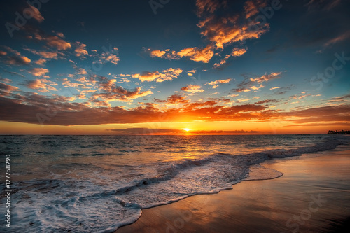 Canvas Prints Cappuccino Sunrise over the beach. Waves washing the sand.