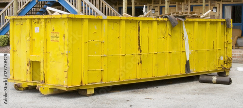 Huge yellow industrial dumpster full of construction and renovation debris in motel parking lot Canvas Print