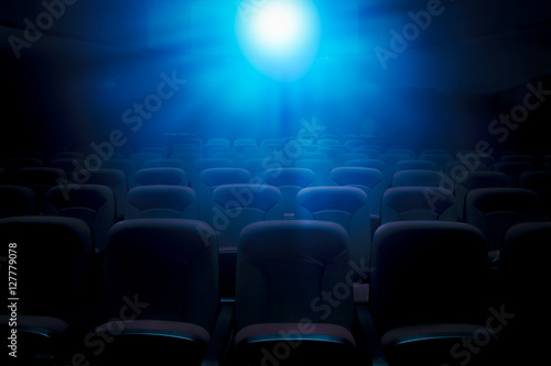 Photo  Dark film theater with projection light and empty seats