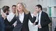Beautiful business lady dancing with champagne flute with her colleagues in the office