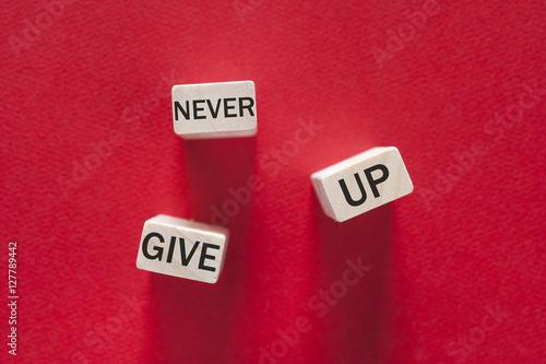 Never give up. Motivational message written on wooden tiles