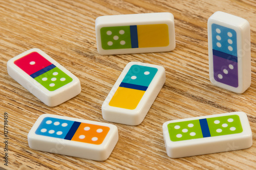 Domino pieces on the  wooden table background плакат