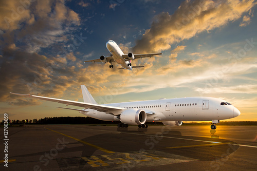White passenger airplane on airport runway during sunset Wallpaper Mural