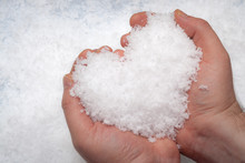 Man Holding With Both Hands A Snowball Shaped Like A Heart Against The A Background Of White Snow