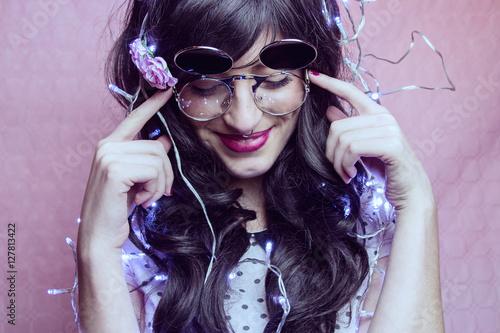 Fotografie, Obraz  Chica hipster joven y guapa pasándolo bien en una fiesta decorada con luces de n