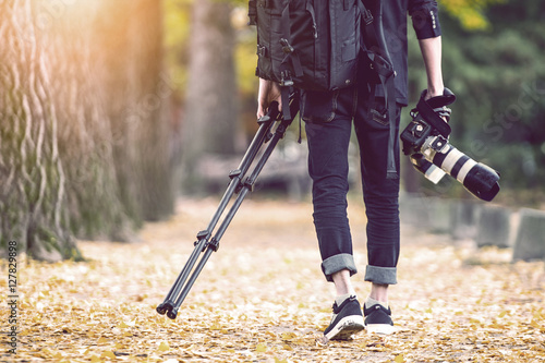 Foto op Aluminium Aubergine professional photographer with camera and tripod in autumn. Vintage tone.