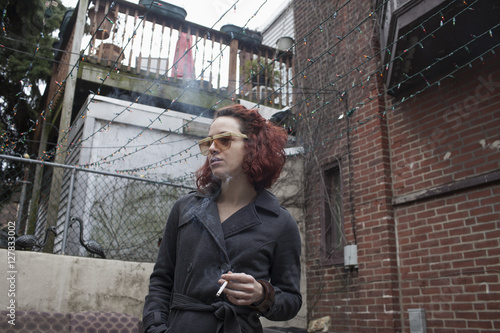 Young woman smoking cigarette while standing outdoors - 127833002