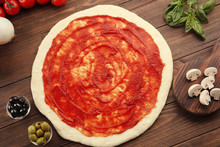 Raw Pizza Dough With Sauce And Ingredients On Wooden Table